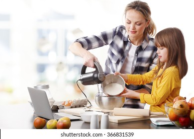 Portrait of adorable little girl and her mother cooking together at home. Happy mom and her cutie daughter using kitchen robot while mixing the ingredients.