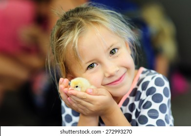 A portrait of an adorable little girl, preschool or school age, happy child holding a fluffy yellow baby chicken  with both hands and smiling