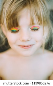 Portrait of adorable little girl with rainbow painted eyelids