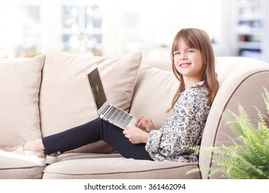 Portrait of adorable little girl using laptop while sitting at home on the sofa.