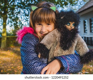 Portrait of adorable little girls with her favorite doll-puss.