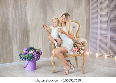 Portrait of adorable mother and cute daughter lovely hugging each other posing on retro chair with bouquet of flowers