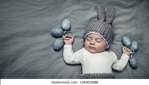 Portrait of an adorable newborn child dressed in a knitted costume of an Easter bunny with stylish colored eggs, copy space, Easter ideas for kids