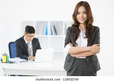 Portrait of an adorable office lady posing for the camera while her male associate working in the background