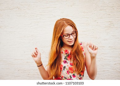Portrait of adorable preteen kid girl of 10-11 yers old with long red hair, wearing eyeglasses