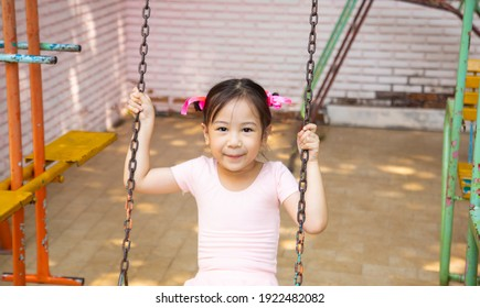 Portrait of adorable and pretty asian girl in pink ballet dress playing alone in playground for swing and climbing shows happiness and enjoyment outdoor activity of children with positive thought.