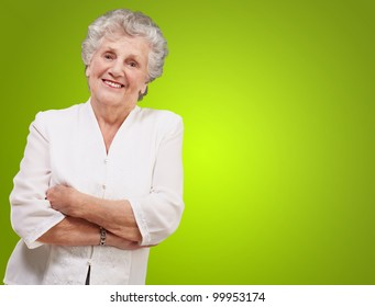 portrait of an adorable senior woman standing over a green background