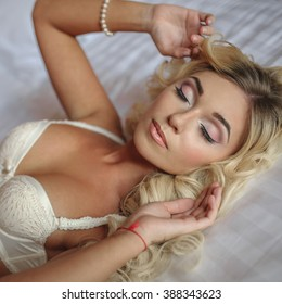 portrait of adorable sexy young bride is laying in white lingerie on the bed with wedding bouquet and close her eyes
