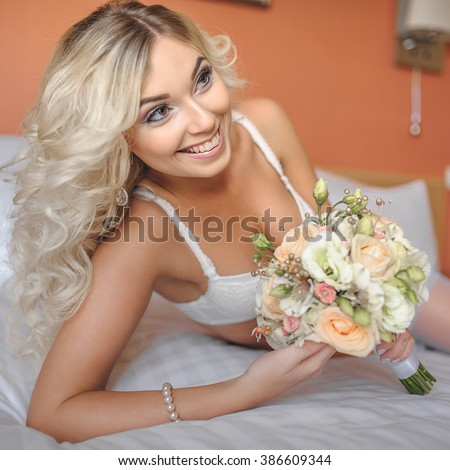 b12162e38b2 portrait of adorable sexy young bride is laying in white lingerie on the  bed with wedding bouquet and looking at copy space - Image