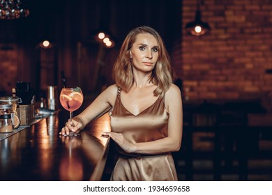 Portrait of adorable slim and beautiful model wearing golden dress and drinking cocktail at the bar in the club. Night club concept