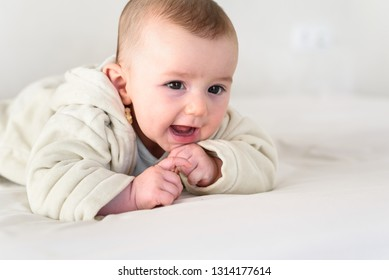 Portrait of an adorable smiling baby holds head up, dressed in pajamas.