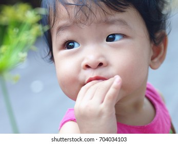 Portrait of adorable smiling little Asian baby girl chewing her fingers in the garden