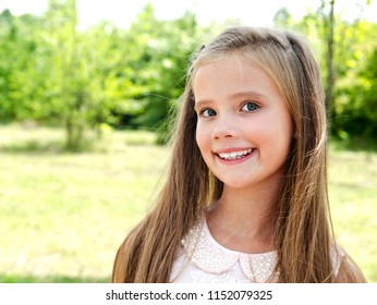 Portrait of adorable smiling little girl outdoors in summer day