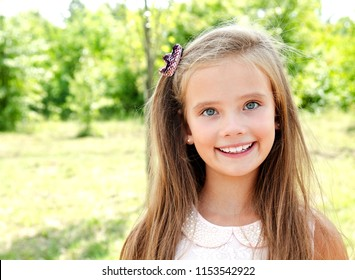 Portrait of adorable smiling little girl child outdoors in summer day