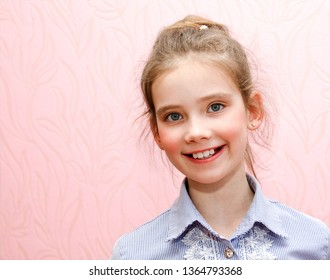 Portrait of adorable smiling little girl schoolgirl child isolated on a pink background