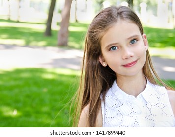 Portrait of adorable smiling little girl child schoolgirl teenager outdoors in summer day