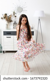 Portrait of adorable smiling little girl child in dress dancing in the room