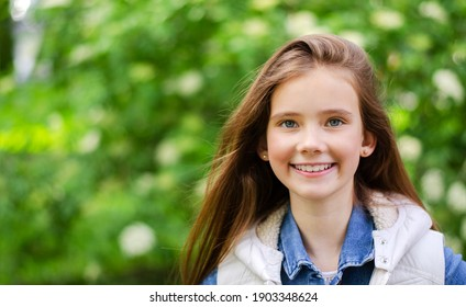 Portrait of adorable smiling little girl child pre teen in the park outdoors