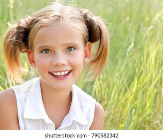 Portrait of adorable smiling little girl child in dress outdoor in summer day