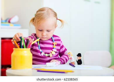 Portrait of adorable toddler girl coloring with pencils