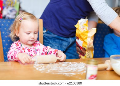 Portrait of adorable toddler girl helping with baking at kitchen