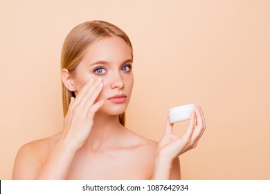 Portrait of adorable, trendy, stylish model having white jar with effective cream, applying under eyes, botox effect, fighting with dark circles, looking at camera isolated on beige background