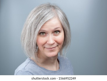 Portrait of an adorable woman with grey hair in her early fifties