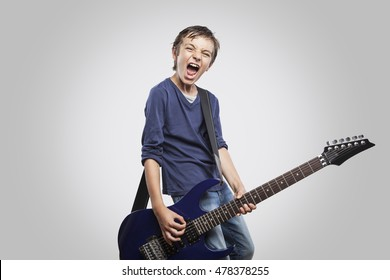 Portrait of adorable young boy playing electric guitar. Rock and roll kid