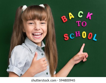Portrait of adorable young girl showing thumb up sign at the green chalkboard in classroom.