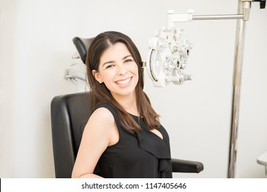 Portrait of adorable young woman sitting on patient seat with phoropter for eye test checkup in clinic