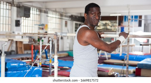 Portrait of adult african man training on gymnastic equipment in gym