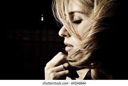 Portrait of adult attractive woman indoor in dark room