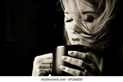 Portrait of adult attractive woman indoor in dark room drinking coffee