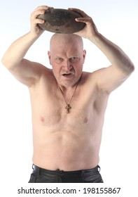 portrait of adult bald man with a naked torso throws a big round stone and shouts on white background studio
