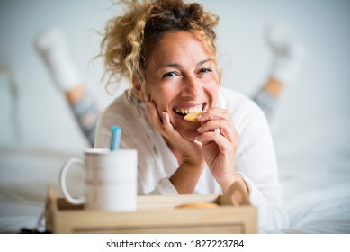 Portrait of adult beautiful woman eating cookie in morning breakfast in the bedroom - home or hotel wake up day with pretty female people lay down with biscuit and tea - cheerful and happy face lady