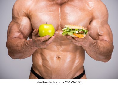 Portrait of adult bodybuilder is holding apple in his hand and hot dog. Healthy lifestyle.
