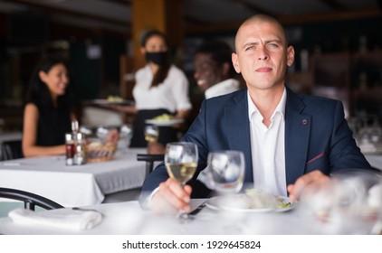 portrait of adult businessman sitting in restaurante