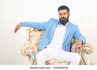 Portrait of adult businessman wearing blue jacket and white pants trendy suit and sitting modern studio on armchair Handsome confident bearded man sitting in luxury white chair hipster in elegant suit
