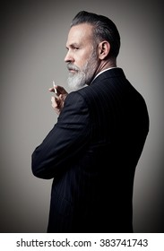 Portrait of adult businessman wearing trendy suit and holding cigarette against the empty wall. Vertical mockup