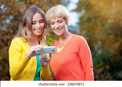 Portrait of Adult caucasian daughter showing on mobile phone to her senior mother outdoor in nature