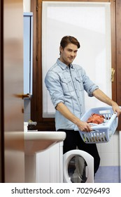portrait of adult caucasian man leaning on washing machine and looking at camera with clothes basket. Vertical shape, side view