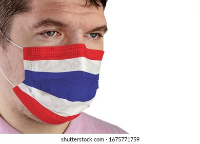 Portrait of adult caucasian man who wears protective mask on his face against influenza and protect health from bacteria. Flag of Thailand. Medical concept to protect health from the virus.