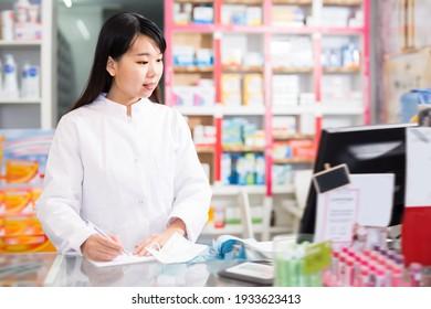 Portrait of adult chinese female pharmacist in modern pharmacy
