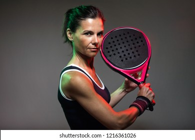 Portrait of adult fitness woman looking at camera while playing padel indoor. Isolated on black.