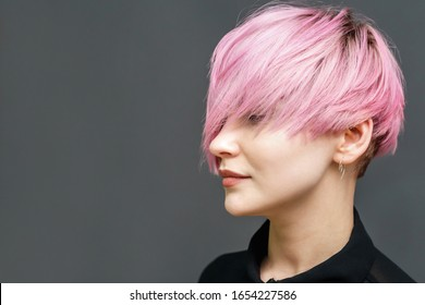 Portrait of adult girl with modern short pink hairstyle and closed eyes on the gray background with copy space.