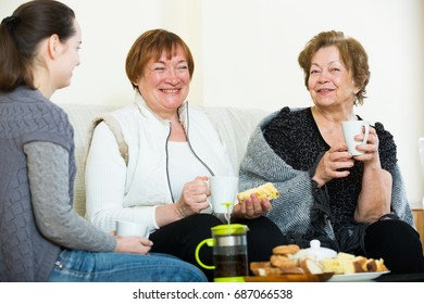 Portrait of adult girl and two pensioners drinking tea together