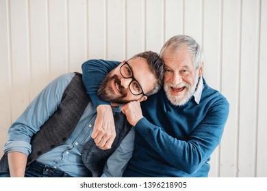 Ein Portrait von erwachsenen Hippistersohn und Seniorvater sitzend auf dem Boden drinnen zu Hause.