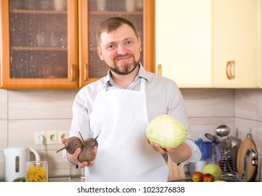 Portrait adult male vegetarian holds cabbage and beets in his hands. A middle-aged man in the kitchen prepares a vegetable dish.