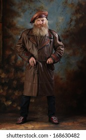 Portrait of an adult man with a beard and mustache in a leather coat and a beret, a stern look, standing the studio on a brown-blue background
