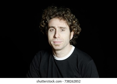 Portrait of adult man with curly hair on a black backdrop